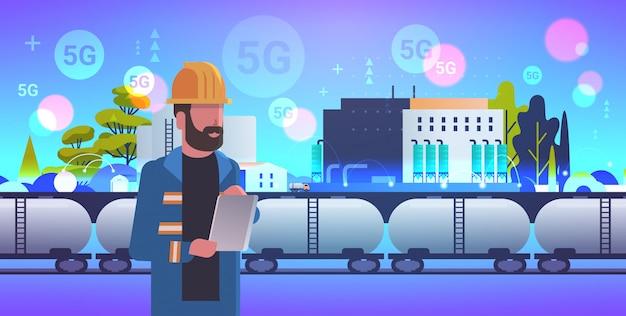 タブレットを使用して男性エンジニアは、油と燃料の5 gオンラインワイヤレスシステム接続工場建物工業地帯プラント発電所概念水平肖像画と鉄道タンクを制御します。