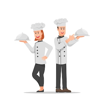 Male and female chefs posing with covered dishes