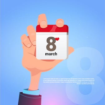 Male hand holding calender page with 8 march date happy international women day holiday concept