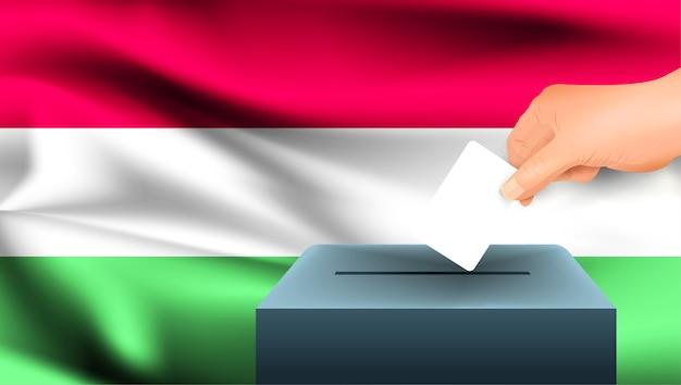 남성 손은 헝가리 국기의 배경에 대해 투표 용지의 상징으로 표시가있는 흰색 용지를 내려 놓습니다. 헝가리 선거의 상징