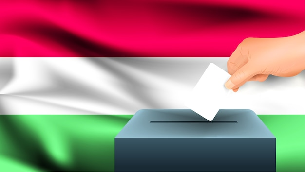 Male hand puts down a white sheet of paper with a mark as a symbol of a ballot paper against the background of the hungary flag. hungary the symbol of elections