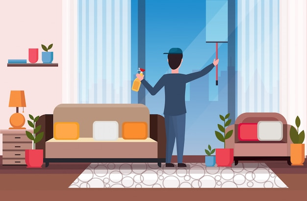 Male janitor using shower wiper squeegee and spray plastic bottle man cleaner wiping glass window cleaning service concept modern living room interior full length flat horizontal