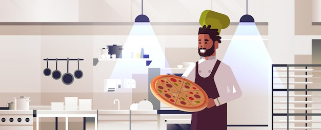 男性のプロのシェフが新鮮なピザアフリカ系アメリカ人の男を均一な調理食品コンセプトモダンなレストランキッチンインテリアポートレートで保持