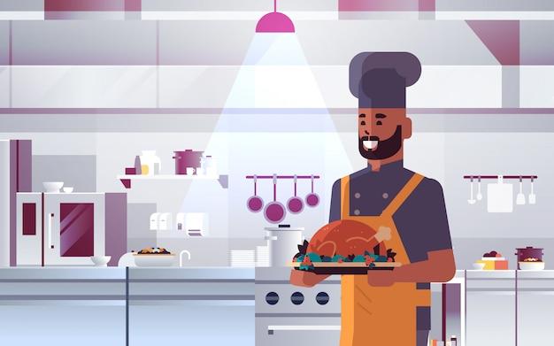 男性のプロのシェフがローストチキンの男性と制服を着てトレイを保持しているトレイ感謝祭トルコ料理食品コンセプトモダンなレストランキッチンインテリアポートレート