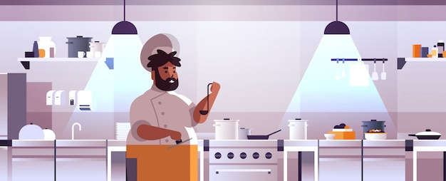 Male professional chef cook preparing and tasting dishes african american man in uniform near stove cooking food concept modern restaurant kitchen interior portrait