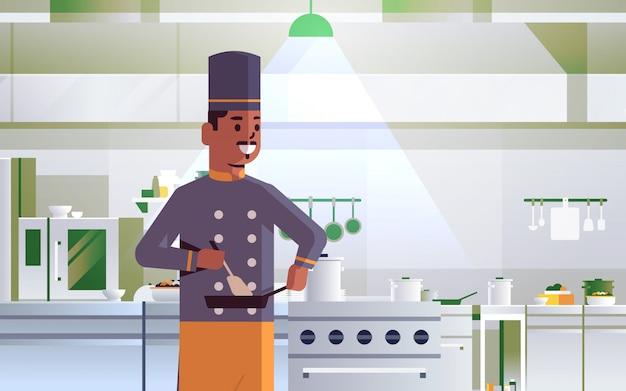 ストーブ調理コンセプトモダンなレストランキッチンインテリアの肖像画の近くに立っている制服を着たアフリカ系アメリカ人男性がフライパンをかき混ぜるフライパンを使用して男性のプロのシェフ