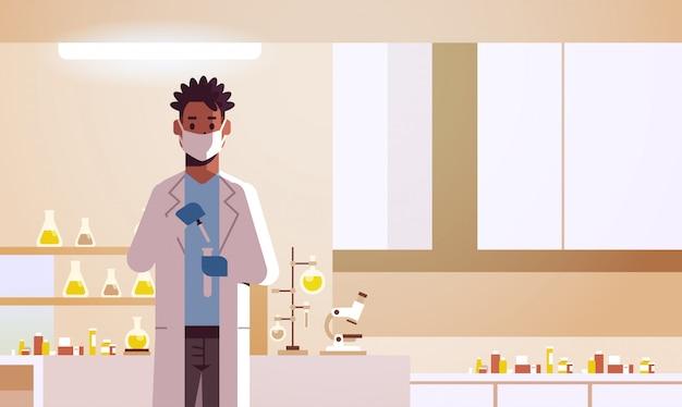 Научный сотрудник мужского пола, держащий пробирку