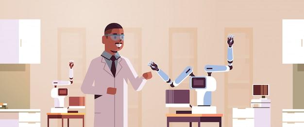 Мужчина ученый возле промышленной роботизированной руки