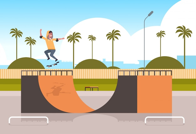 Male skater performing tricks in public skate board park with ramp for skateboarding teenager having fun riding skateboard landscape background flat full length horizontal