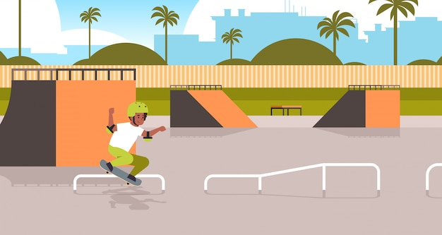 Male skater performing tricks in public skate board park with ramp for skateboarding teenager having fun riding skateboard landscape