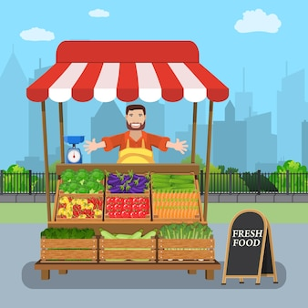 Уличный продавец-мужчина продает овощи из своего ларька на городской улице
