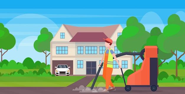 産業用掃除機を使用して男性のストリートワーカーの男がゴミの掃除サービスコンセプトモダンなコテージの家の田舎の背景全長フラット水平を掃除