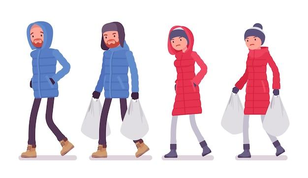 重い買い物袋を持ったダウン ジャケットを着た男女、柔らかい暖かい冬の服、クラシックなスノー ブーツと帽子を着ている