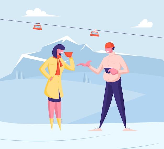 Мужчина и женщина в теплой одежде пьют горячие напитки на горном пейзаже