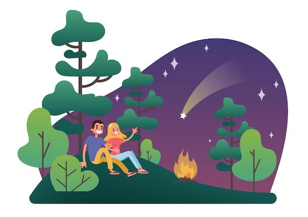 남자와 여자는 모닥불에 잔디에 앉아