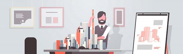 도시 패닝 프로젝트에 대한 새로운 건물 도시 모델로 작업하는 남자 건축가 지주 레벨 엔지니어