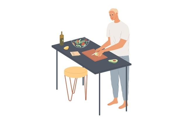 Мужчина дома готовит овощной салат, режет авокадо.