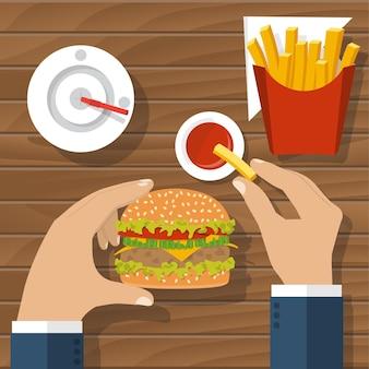 패스트 푸드, 햄버거, 감자 튀김, 음료 콜라와 토마토 소스, 상위 뷰를 먹는 테이블에서 남자