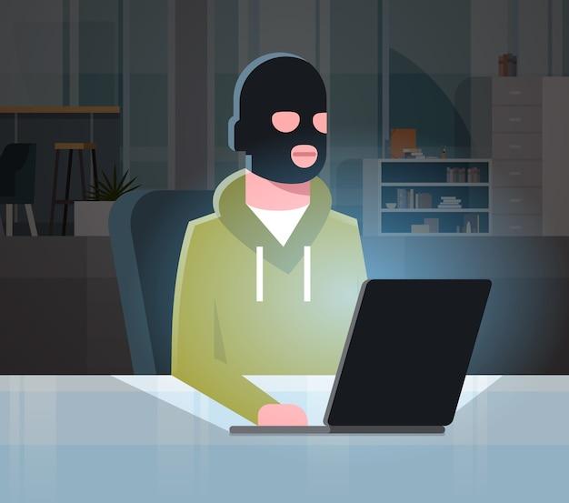 Человек черная маска сидит на компьютере