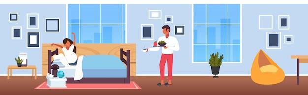 妊娠中の女性がベッドの上に座って妊娠中の女性のための食物と一緒に朝食トレイをもたらす男現代家の寝室のインテリア将来の両親の愛幸せ家族概念全長水平