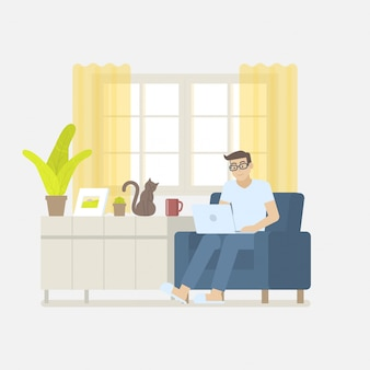 Man in casual clothing working at home with laptop computer on armchair in living room