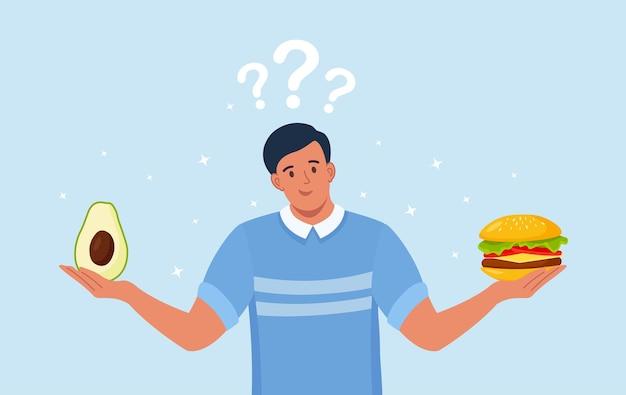 健康食品と不健康食品のどちらかを選ぶ男性。ファーストフードとバランスの取れたメニューの比較、ダイエット。良い栄養と悪い栄養の選択