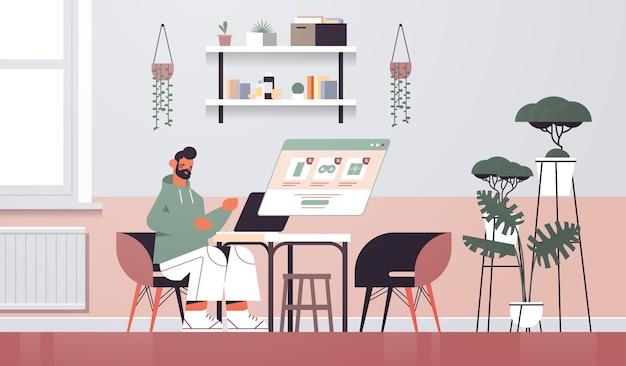 ノートパソコンの画面で商品を選ぶ男オンラインショッピングサイバーマンデー大セール休日割引eコマースコンセプトリビングルームインテリア