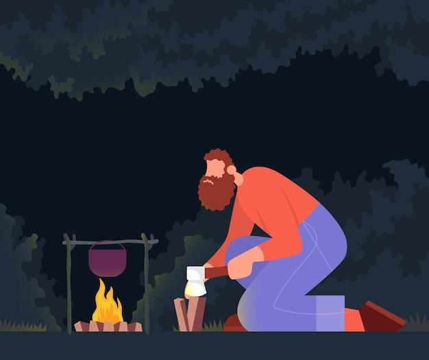 夜の森でたき火のために薪割りの男ライフスタイルコンセプト野外活動