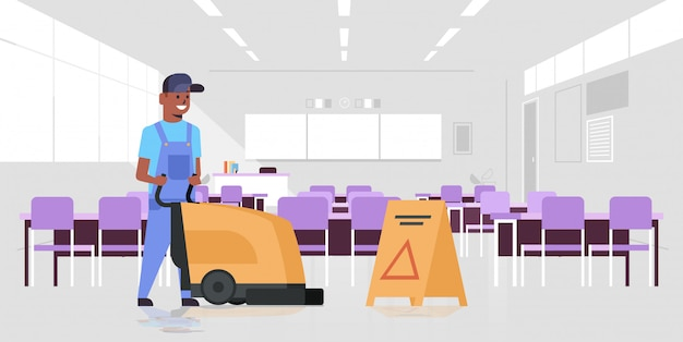 Man cleaner using professional washing machine   janitor in uniform with wet floor sign cleaning service concept modern school classroom interior  full length horizontal
