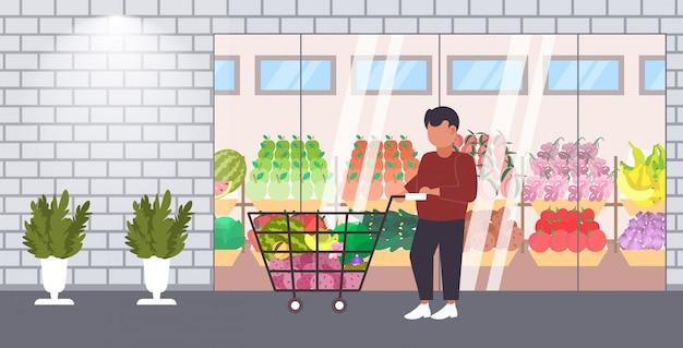 食料品の野菜や果物のショッピングコンセプトモダンな食料品店スーパーマーケット外観全長水平トロリーカートを押す男性客