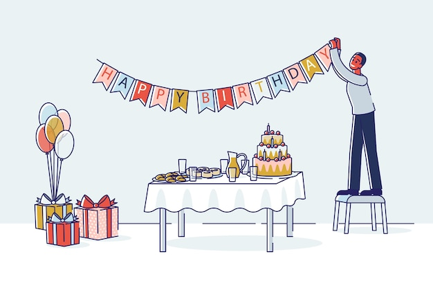 Man decorating room for birthday celebration hanging holiday garland above table with cake.