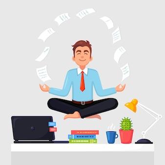 オフィスの職場でヨガをしている男性。飛んでいる紙でパドマサナ蓮のポーズに座っている労働者