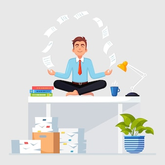 Man doing yoga at workplace in office. worker meditating, relaxing on desk with flying paper