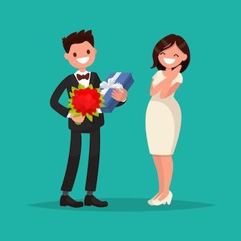 Мужчина в костюме дарит женщине букет цветов и подарок.