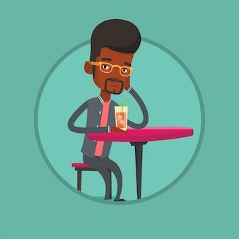 バーでカクテルを飲む男性。