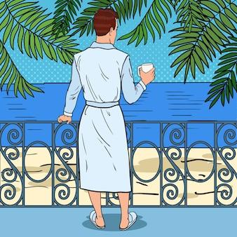 バルコニーでコーヒーを飲む男性