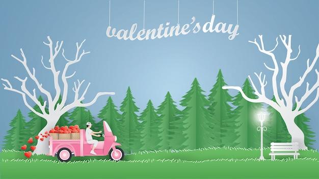 Мужчина за рулем розового мини-грузовика на трех колесах несет сердца на зеленой траве в городе