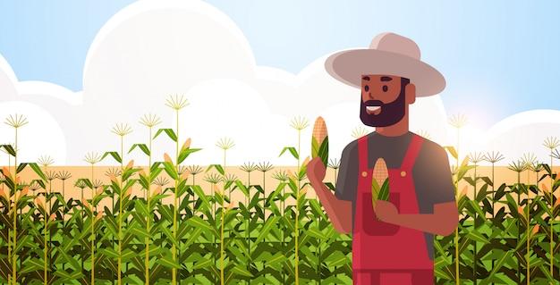 トウモロコシ畑の有機農業の上に立ってのオーバーオールでトウモロコシの穂軸の同国人を保持している男の農家