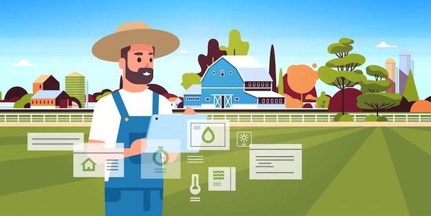 タブレットモニタリング条件を持つ男の農家収穫のスマートファーミングの概念の農産物組織を制御する農家の建物の風景の肖像画