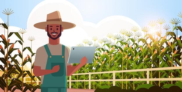 農産物を制御するトウモロコシ畑の状態の田舎人を監視するタブレットを持つ男農家