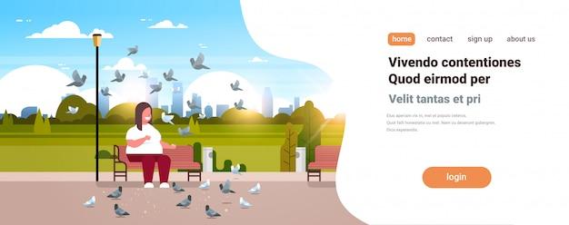 ハトの群れに餌をやる男は都市の都市公園のリラックスできるサイズのベンチに座っている文字を笑顔でリラックス