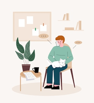 Man freelancer. man holding a cat, talking on the phone. telecommuting at home.