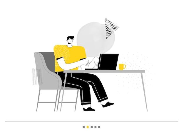 男フリーランサーは椅子に座ってラップトップで作業しています