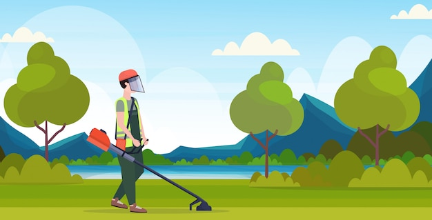 Man gardener in uniform cutting grass with brush cutter gardening concept beautiful nature landscape background full length flat horizontal