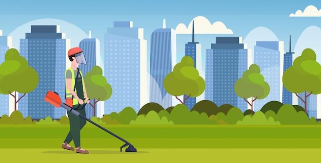 Man gardener in uniform cutting grass with brush cutter gardening concept modern cityscape background full length flat horizontal