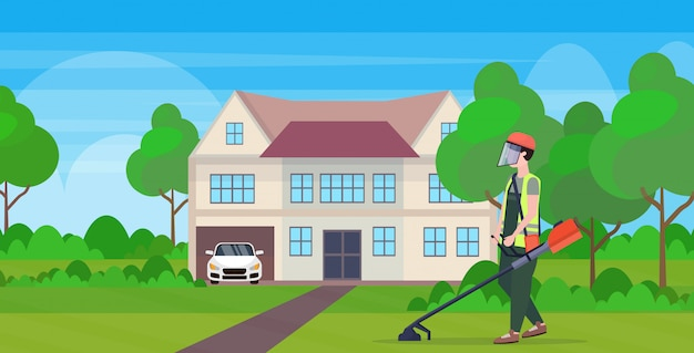 Man gardener in uniform cutting grass with brush cutter gardening concept modern cottage house countryside background full length flat horizontal