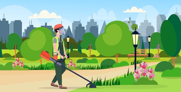 Man gardener in uniform cutting grass with brush cutter gardening concept urban city park cityscape background flat full length horizontal