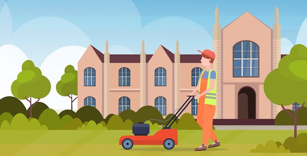 Man gardener in uniform cutting grass with lawn mower gardening concept front yard university building exterior flat full length horizontal