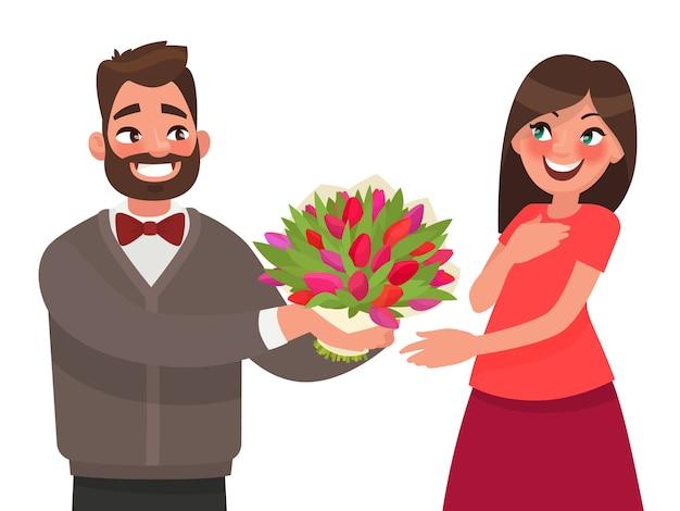 남자는 여자에게 꽃의 꽃다발을 제공합니다. 휴일이나 생일을 축하합니다.