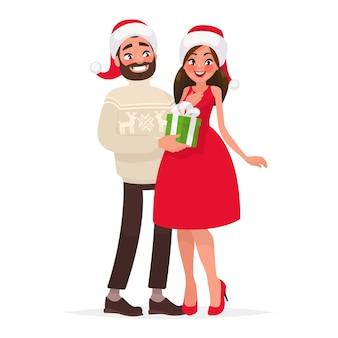 Мужчина дарит женщине подарок на рождество